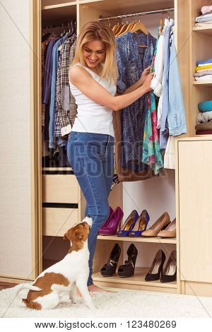 Beautiful girl is smiling and looking at camera standing with crossed arms in a dressing room. A dog is lying near