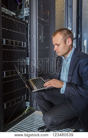 IT Engineer working on a laptop lying in the rack in datacenter