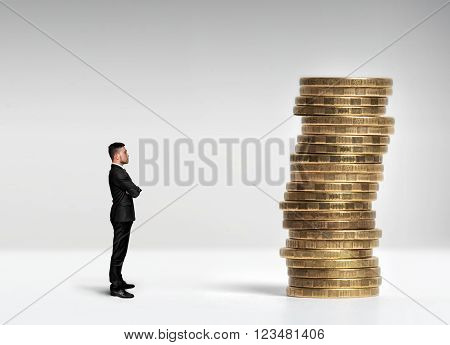 A businessman standing in profile with his arms folded in front of a stack of scale rouble coins. Finance and Investment concept.