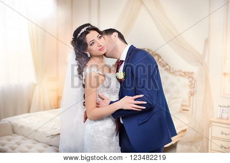 Studio portrait of young elegant enamored just married bride and groom and  embracing on grey background