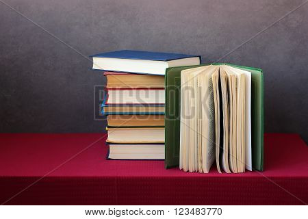 A stack of books in the colored covers on the table with a red tablecloth. Still life with books.