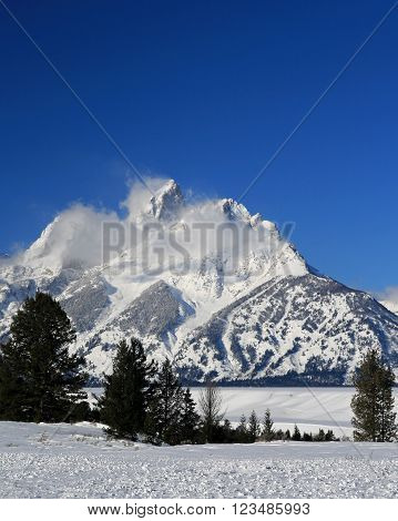 Snow clouds blowing off Grand Tetons peaks in front of snowfield in Grand Tetons National Park in Wyoming USA