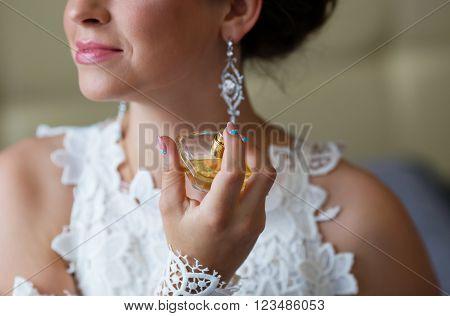 bride applying perfume. Bride spraying perfume on her neck