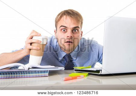 coffee junkie businessman holding take away cup looking with crazy eyes and funny face expression overworked working at office computer desk in caffeine addiction concept