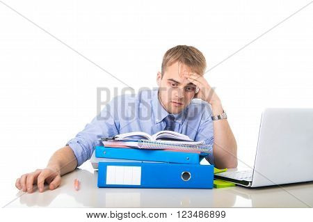 young overworked and overwhelmed businessman in sad and stress face expression reading office folder pile looking exhausted and depressed in business long hours working concept