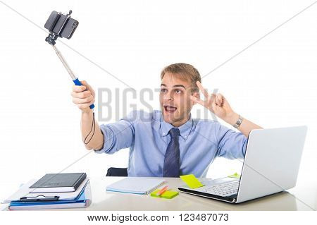 young businessman in shirt and tie sitting at office computer desk holding selfie stick shooting self portrait photo or recording video with mobile phone acting clown and funny