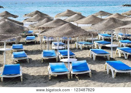 Chairs and umbrellas on Fanabe beach in Tenerife, Spain