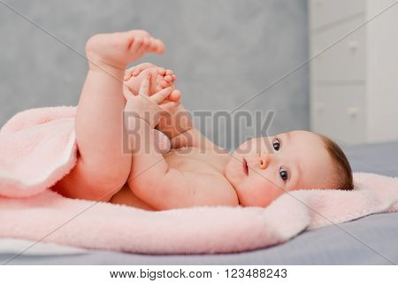 Baby plays with her legs in a pink towel