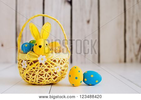 Easter Eggs in a yellow basket with the hare