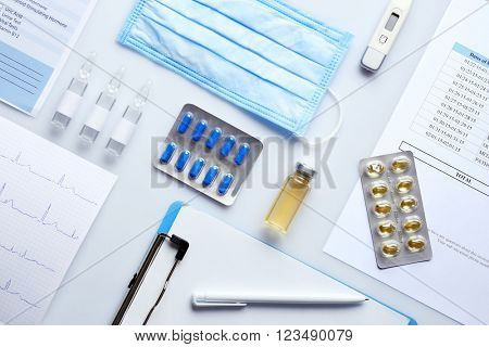 Doctor table with medicines and clipboard, top view