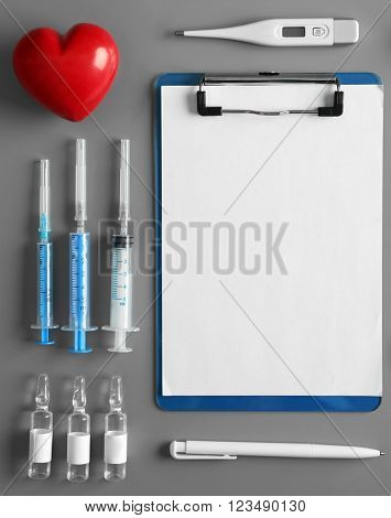 Doctor table with injections, thermometer, clipboard, pen and red heart, top view