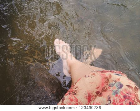 Dreamy fantasy colour lifestyle Women in flowers dress sit and dip feet in crystalline stream summer relaxing feeling