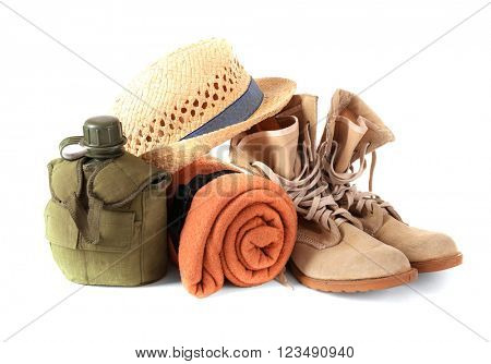 Tourism concept. Pair of boots, rug, hat and canteen isolated on white background