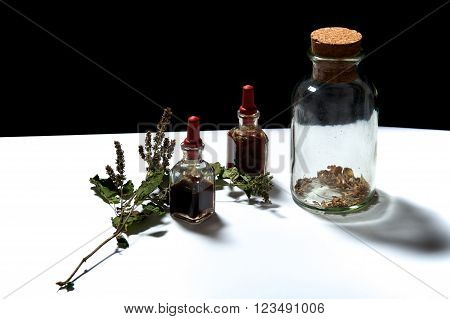 Three Glass Bottles With Herbal Extracts And Dried Herbs