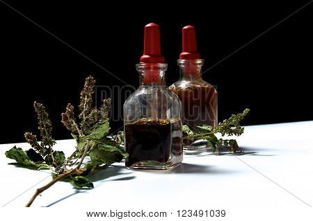 Two Glass Bottles With Herbal Extracts And Dried Patchouli Floewrs