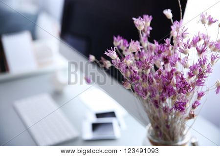 Modern interior. Comfortable workplace. Wooden table with beautiful bouquet of flowers and computer on it, close up