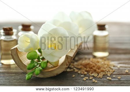Spa set with sea salt, flowers and aroma oil on wooden background