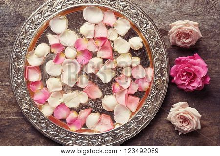 Pink and white rose petals in silver bowl on wooden background