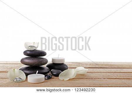 Spa stones with white petals and candles on white background