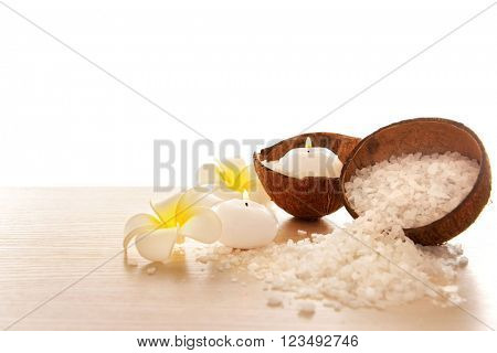 Spa concept of plumeria, coconut and candles with sea salt, isolated on white