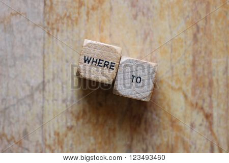 Where to written on two wood dice on open wood grain background for copy