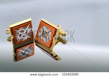gold cufflinks on a mirrored reflective background