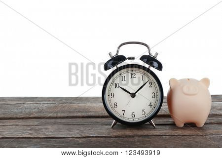 Yellow piggy bank and clock on white background