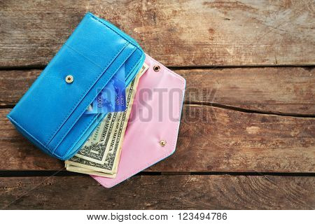 Blue wallet with dollar bills on the wooden background