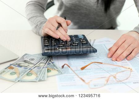 Woman set aside money, papers, her glasses and using calculator on the white wooden table, close up