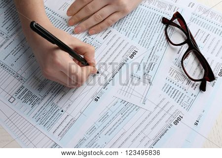 Female hand holding a pen next to the black rimmed glasses and filling in the 1040 Individual Income Tax Return Form for 2015 year on the white desk, close up