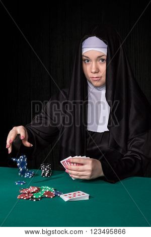 Nun throwing poker chips on the table staking