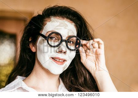 funny young woman applying a deep cleansing clay mask. The woman points