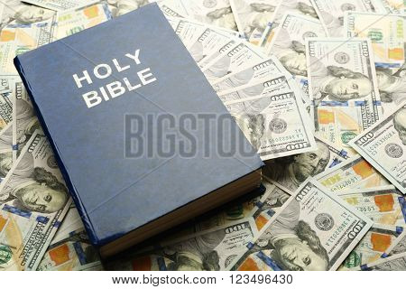 Holy Bible on money background, closeup