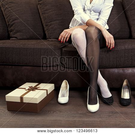 woman trying on several pairs of new shoes in the mall