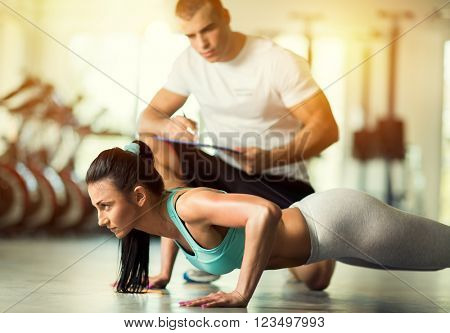 Fit woman doing exercises in presence of a personal instructor