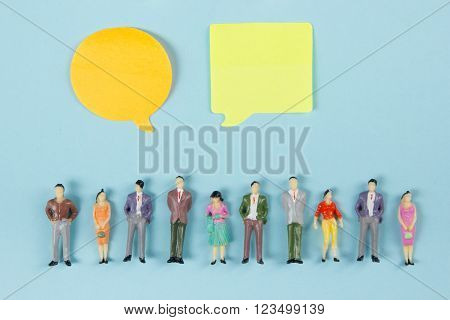 Real Estate concept. Blank speech bubbles and people toy figures Construction, building. Paper model house with key on blue background. Top view. Copy space for text