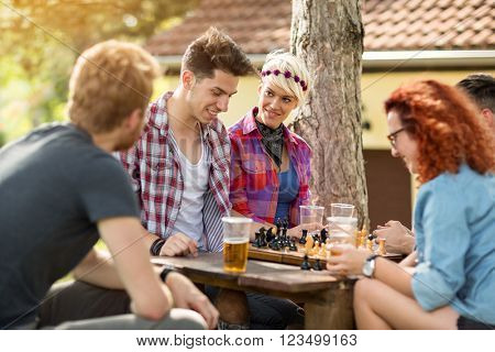 Youth at summer camp in nature amused playing chess and drinking beer
