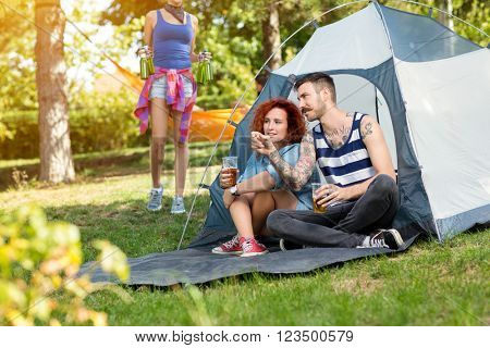 Tattooed guy and lassie sits and drinks beer in front of tent at summer camp in nature