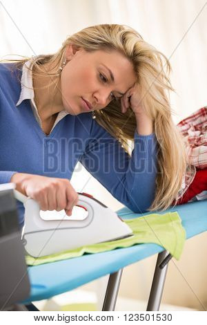 Sometimes ironing is tiring and boring job for young hostess