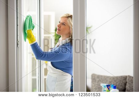Diligent young woman cleans window in apartment