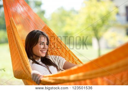 Young smiling girl enjoy in hammock in woods