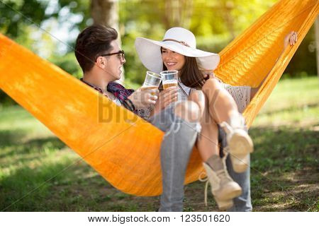 Lovely lassie with boyfriend toast with glasses of beer in hammock in forest