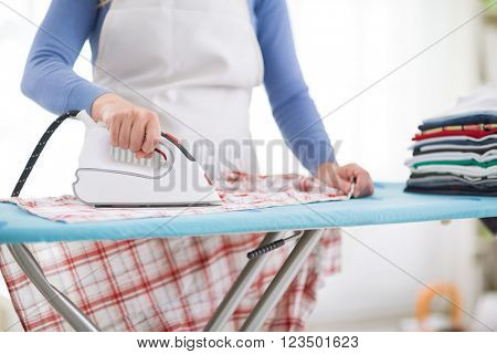 Close up of wife ironing shirt to her husband