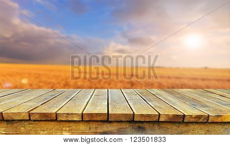 Empty old wooden table for product display montages with field in background