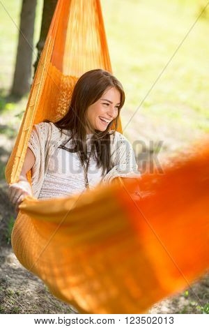 Likeable young woman  lying and enjoying in orange hammock outdoor
