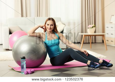 Young sportswoman sitting with ball and bottle of water on a mat at home