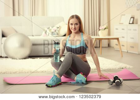 Young sportswoman sitting with  dumbbells and bottle of water on a mat at home