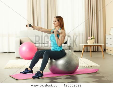 Young sportswoman doing exercises with ball and dumbbells on a mat at home