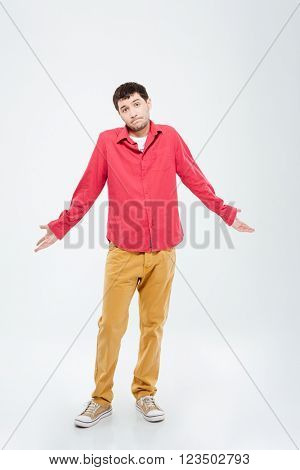 Full length portrait of a young man shrugging shoulders isolated on a white background