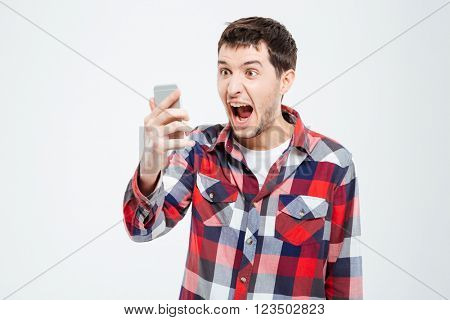 Angry man shouting on smartphone isolated on a white background